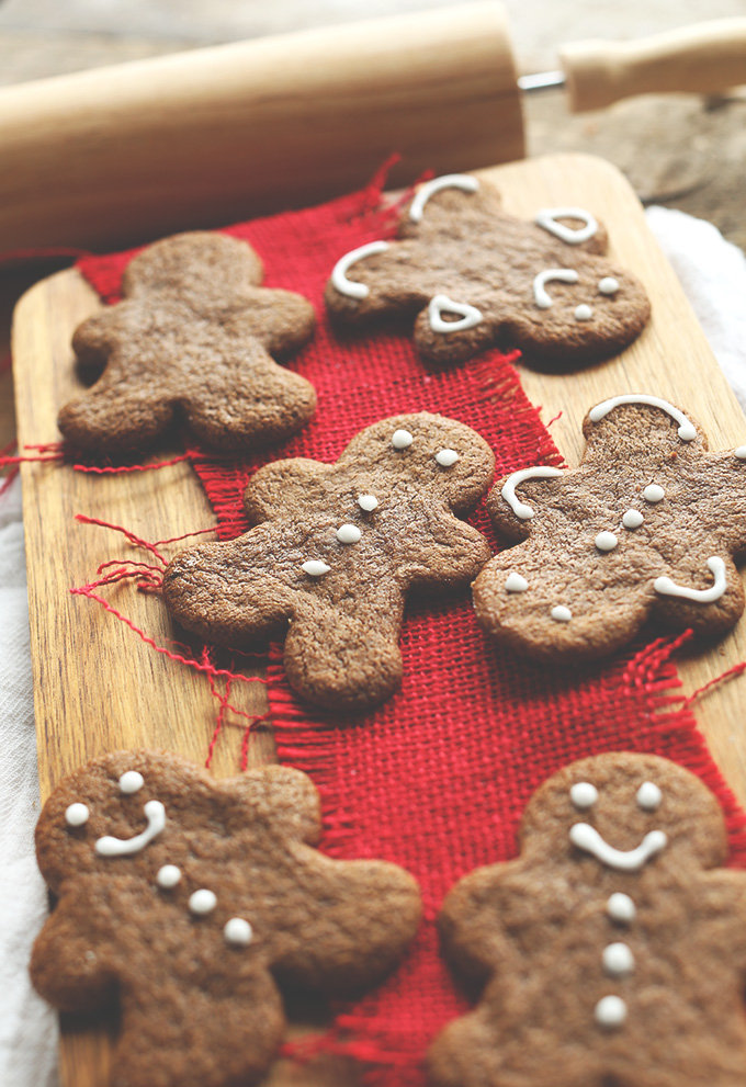 Wood cutting board with a batch of our decorated Gingerbread Cookies