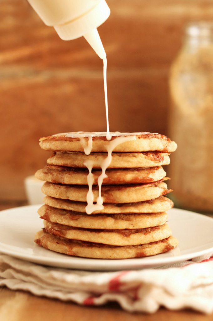 Drizzling icing onto a stack of Fluffy Vegan Yeasted Cinnamon Roll Pancakes