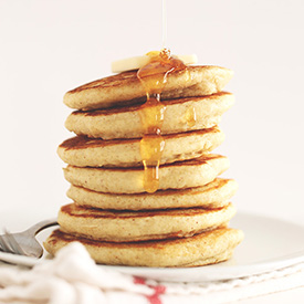 Maple syrup dripping off a stack of pancakes made with our GF Pancake Mix