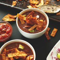 Two bowls of Loaded Veggie Nacho Soup beside bowls of salsa and chopped red onion and lime