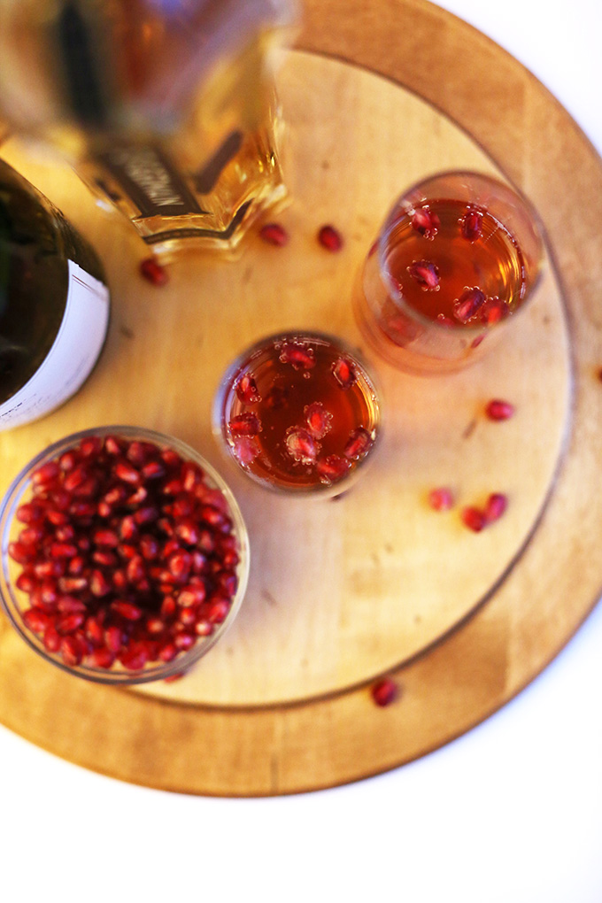 Tall glasses of Pomegranate St. Germain Spritzers surrounded by ingredients used to make them