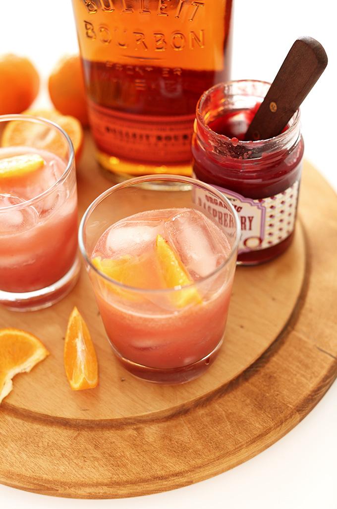 Glasses of Raspberry Jam Bourbon Smash on a wood cutting board