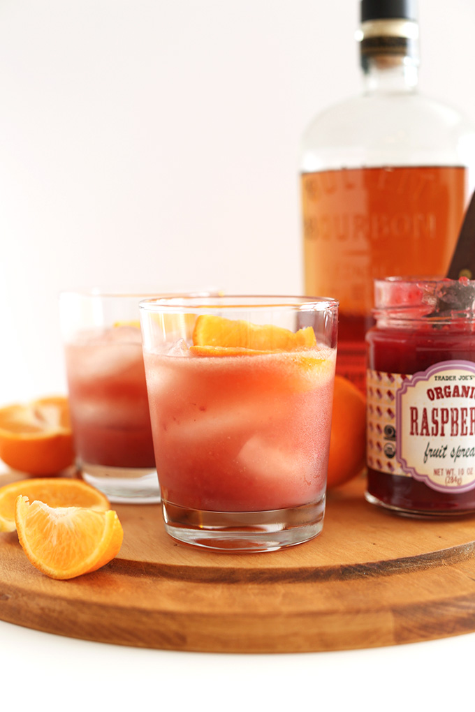 Glasses of our Raspberry Jam Bourbon Smash recipe surrounded by ingredients used to make it