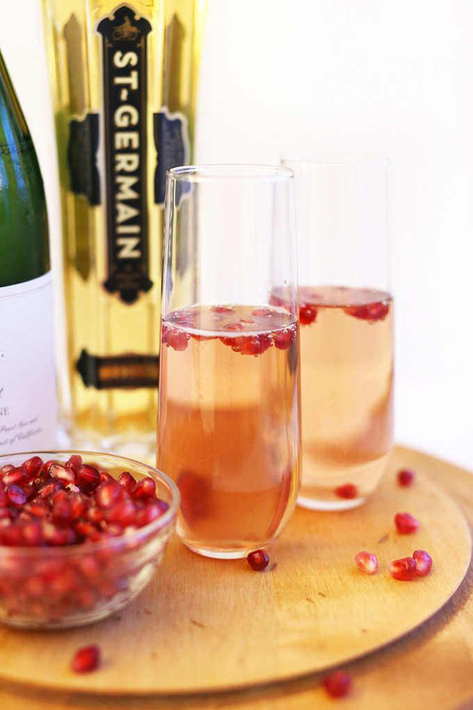 Two tall glasses of St. Germain Spritzers with fresh pomegranate seeds