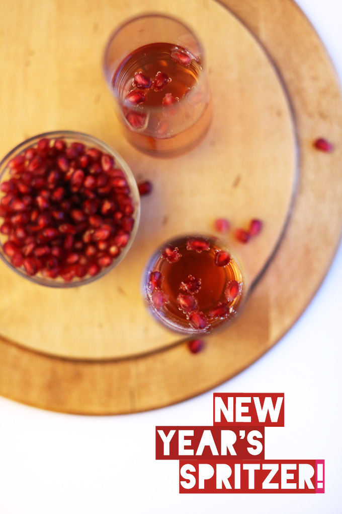 Glasses of St. Germain New Year's Spritzers made with pomegranate seeds