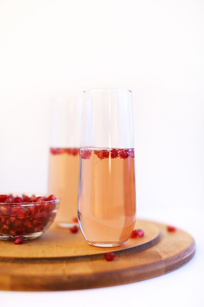Bowl of pomegranate seeds and two tall glasses filled with our Pomegranate Spritzers recipe