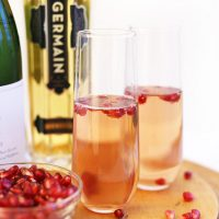 Cutting board with a bowl of pomegranate arils beside fancy glasses filled with our St Germain Spritzers recipe