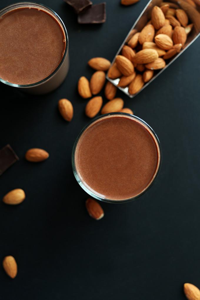 Dark chocolate, almonds, and glasses of homemade Chocolate Almond Milk