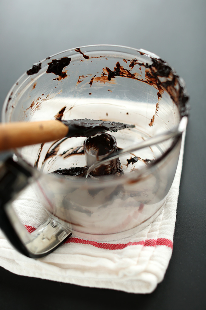 Rubber spatula resting in a food processor scraped of brownie batter