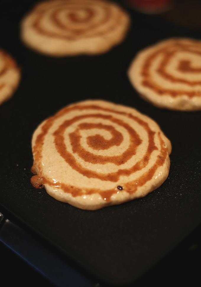 Cooking Vegan Cinnamon Roll Pancakes on a griddle