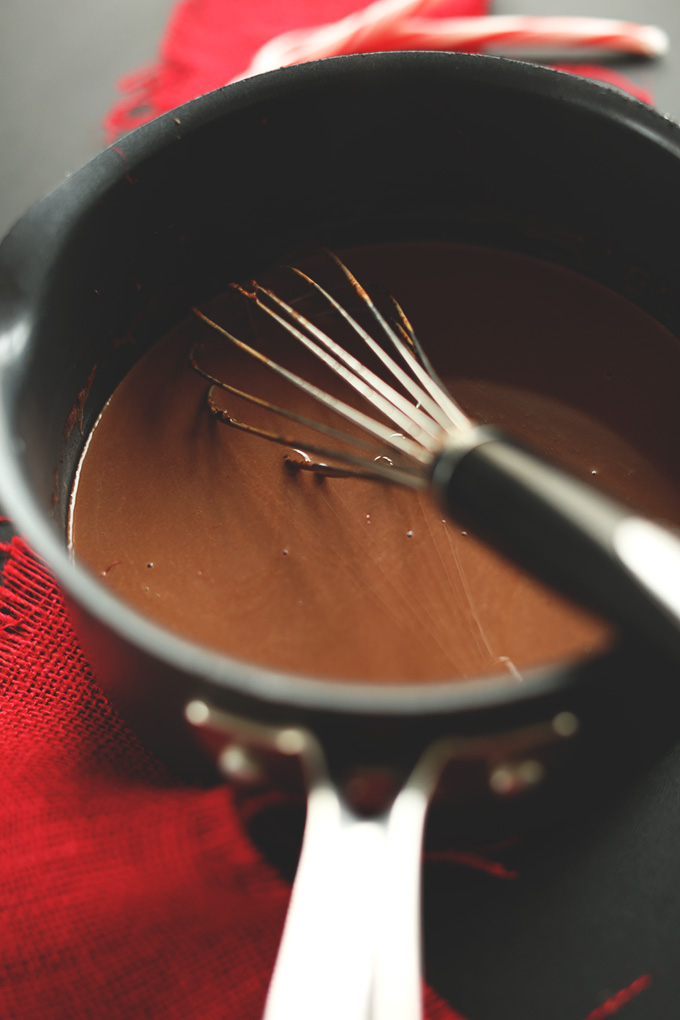 Using a whisk to mix together Vegan Drinking Chocolate ingredients in a saucepan