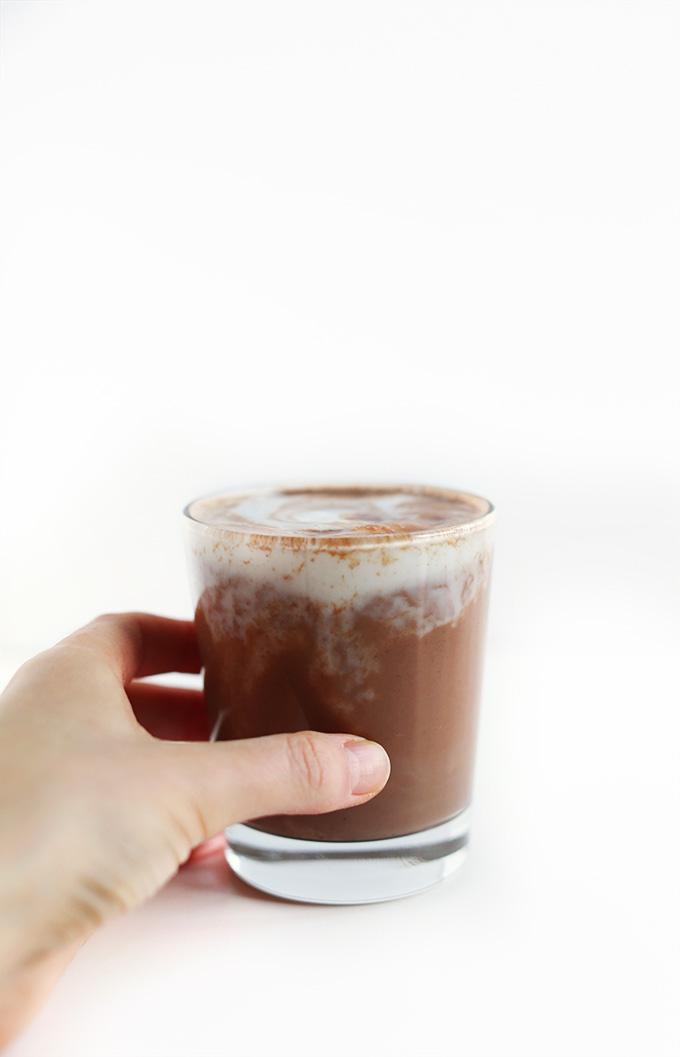 Tomando un vaso de cacao caliente vegano para una bebida de invierno que se calienta