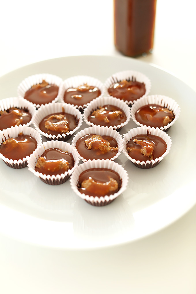 Plate of almond butter cups in process showing the chocolate, almond butter, and caramel layers