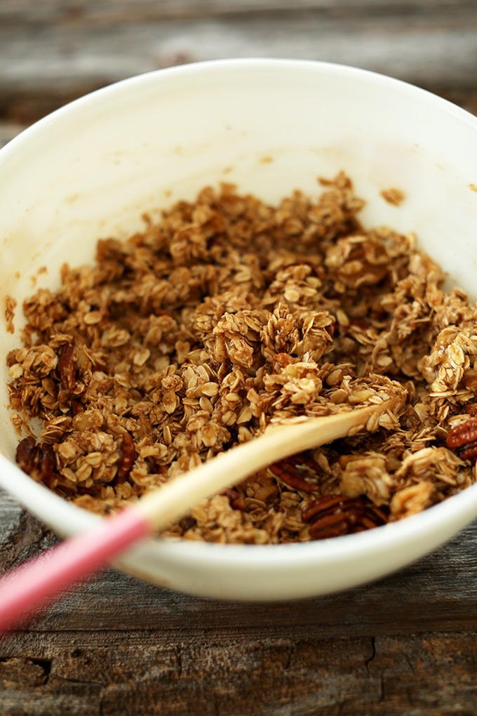 Stirring a bowl of our gluten-free vegan Banana Bread Granola recipe