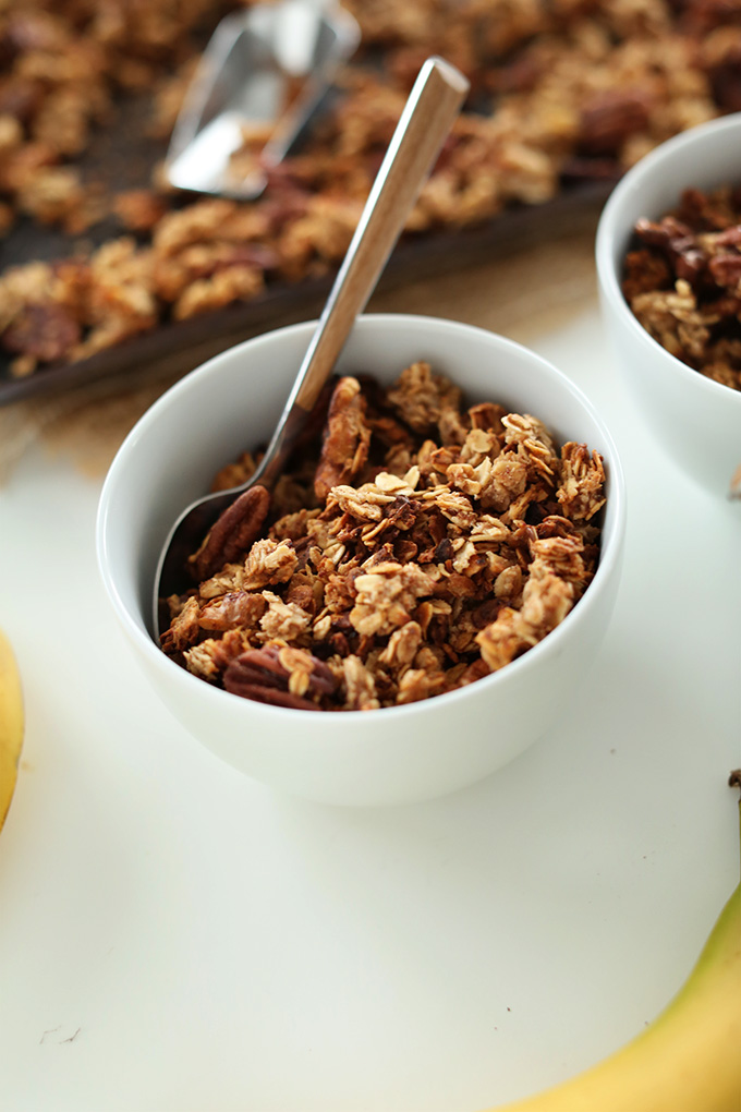 Serving bowls and baking sheet with Banana Bread Granola for a delicious vegan breakfast
