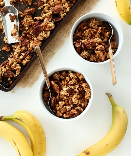 Baking sheet and bowls of Banana Bread Granola alongside fresh bananas
