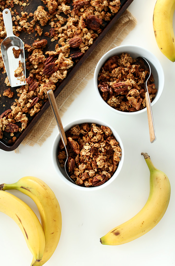 Baking sheet and bowls filled with Banana Bread Granola made with walnuts and flax
