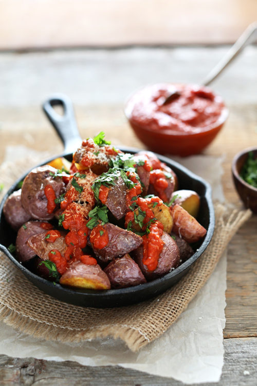 Skillet piled high with Patatas Bravas topped with Spicy Sauce