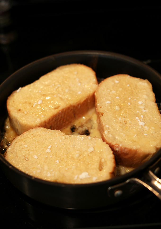 Cooking slices of Coconut Cream Pie French Toast in a skillet