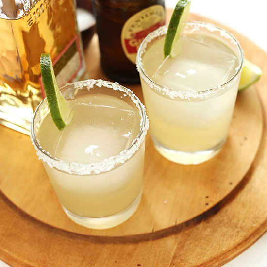 Two homemade Ginger Beer Margaritas on a cutting board
