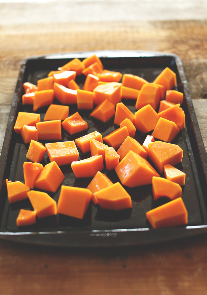 Baking sheet of with chunks of butternut squash ready to be roasted