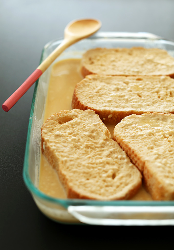 Slices of bread resting in batter for Overnight French Toast