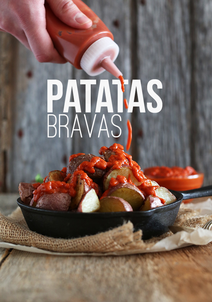 Drizzling sauce onto gluten-free vegan Patatas Bravas