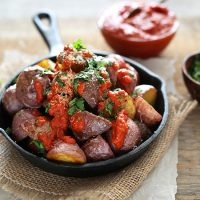 Cast-iron skillet piled high with Patatas Bravas topped with Spicy Sauce