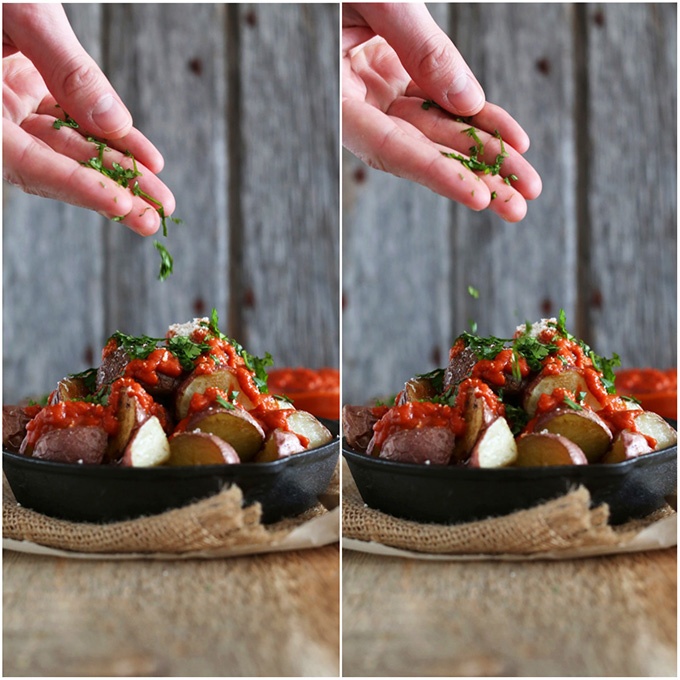 Sprinkling fresh parsley onto a cast-iron skillet filled with Patatas Bravas with Spicy Tomato Sauce