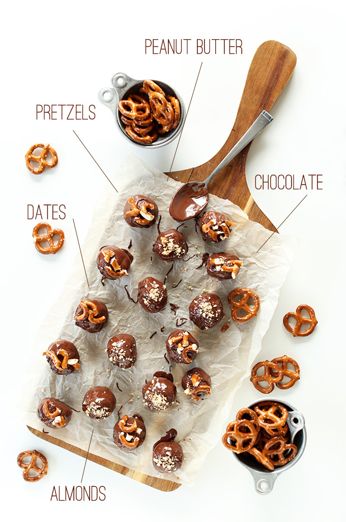 Cutting board filled with Peanut Butter Pretzel Truffles and measuring cups of pretzels