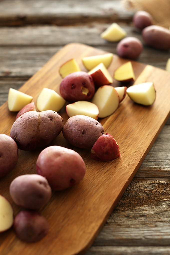 Cutting board filled with an assortment of chopped and whole red skin potatoes