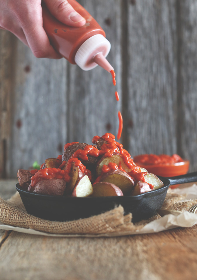 Drizzling sauce onto Patatas Bravas in a cast-iron skillet