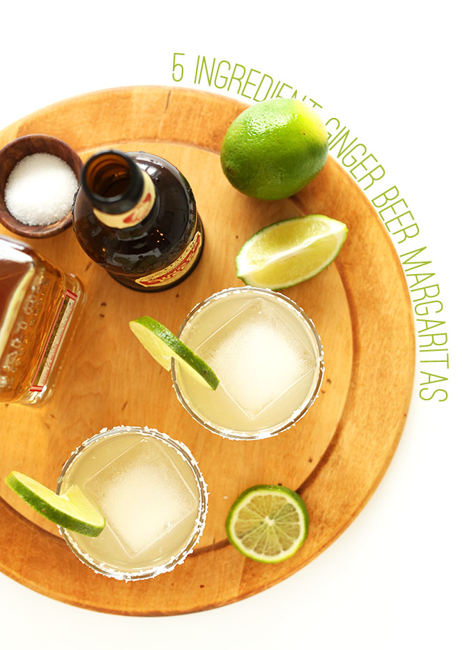 Cutting board with glasses of our Ginger Beer Margaritas with fresh lime slices