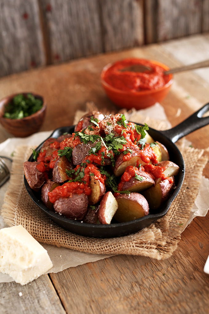 Skillet of Spicy Patatas Bravas with small bowls of extra sauce and parsley