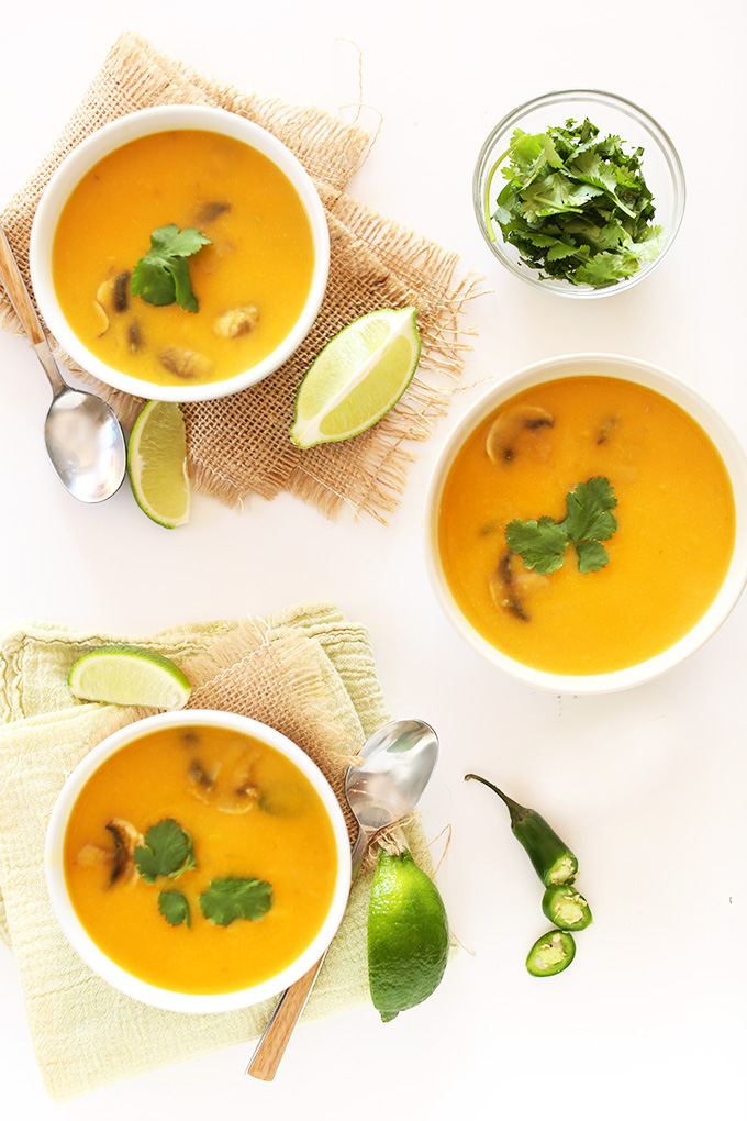 Bowls of Tom Kha Gai Soup with fresh cilantro and lime wedges