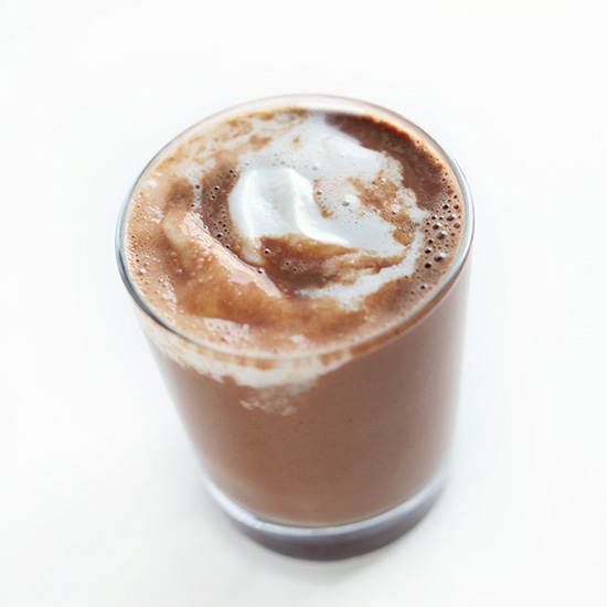 Small glass of Vegan Hot Chocolate topped with coconut whipped cream