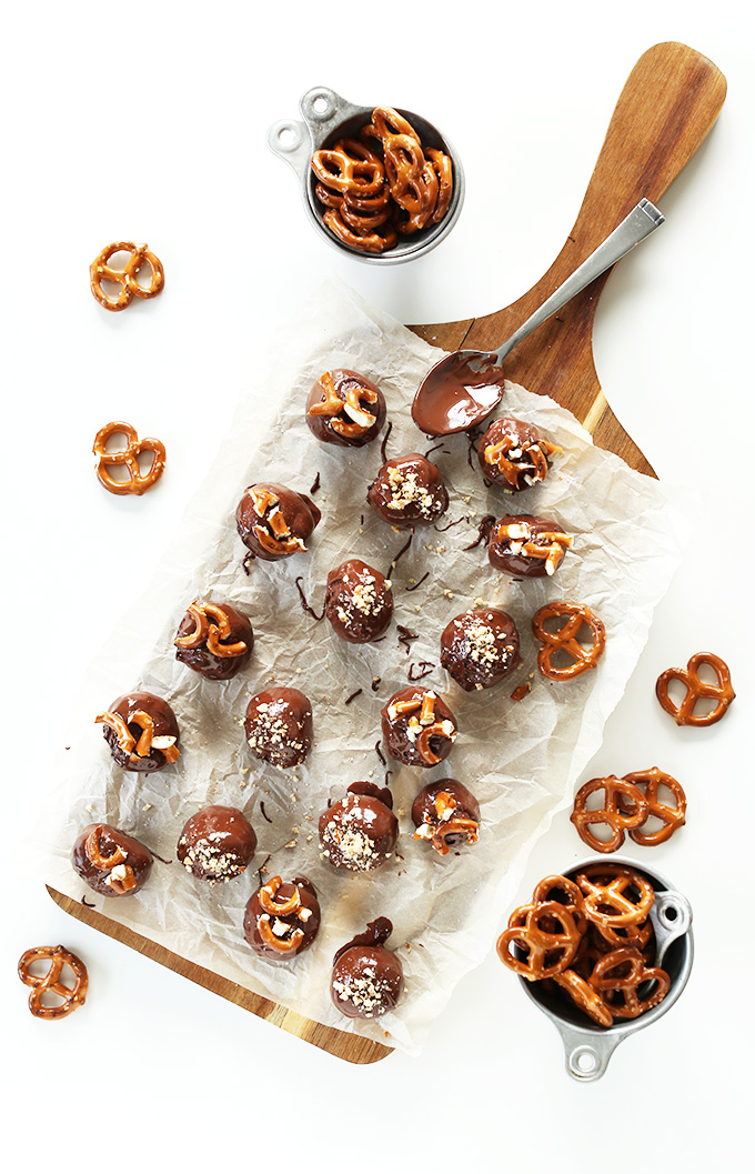 Parchment-lined cutting board filled with Vegan Peanut Butter Pretzel Truffles