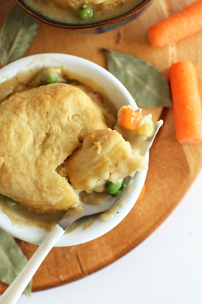 Close up shot of a fork with a bite of Vegan Pot Pie resting on a ramekn