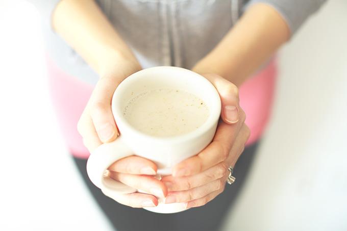 Holding a mug of our homemade vegan Ginger Tea Latte