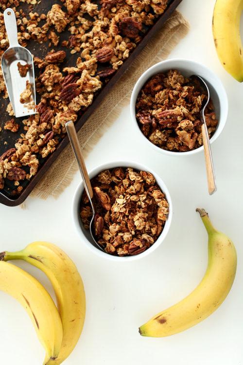 Baking sheet and bowls of Banana Bread Granola alongside fresh bananas