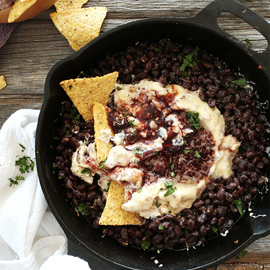 Tortilla chips in and beside a skillet of Black Bean Raspberry Chipotle Dip