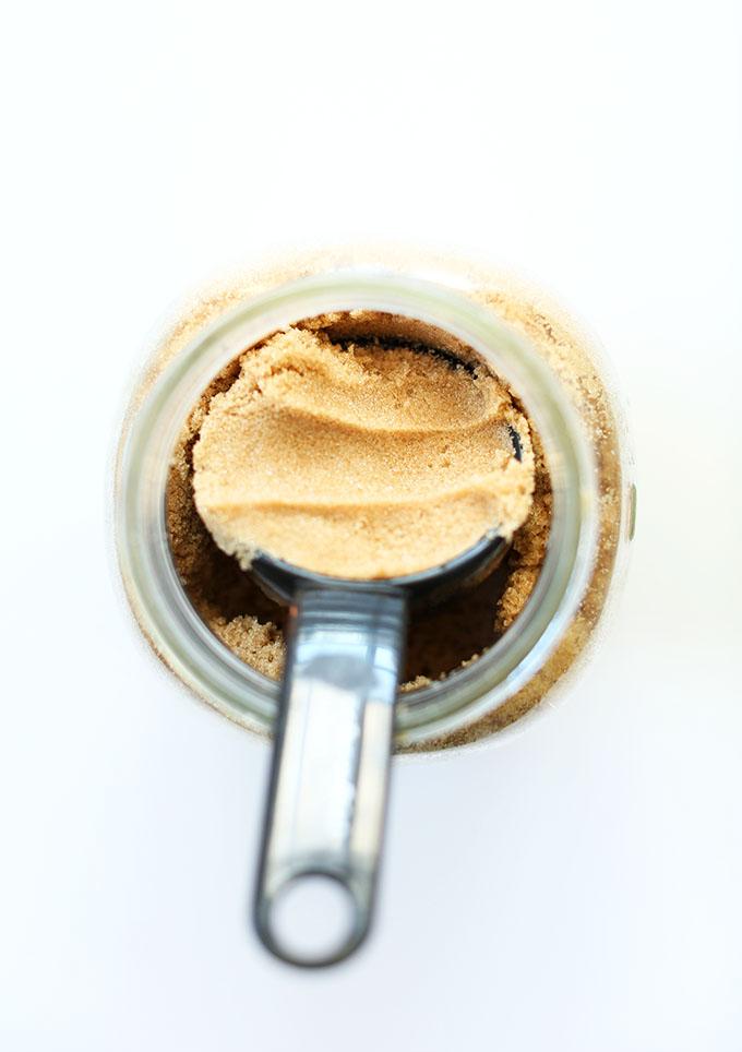 Measuring cup of brown sugar in a glass jar
