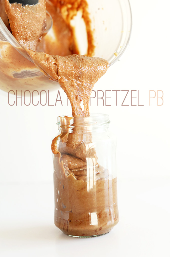 Using a rubber spatula to scoop homemade Chocolate Pretzel Peanut Butter into a jar