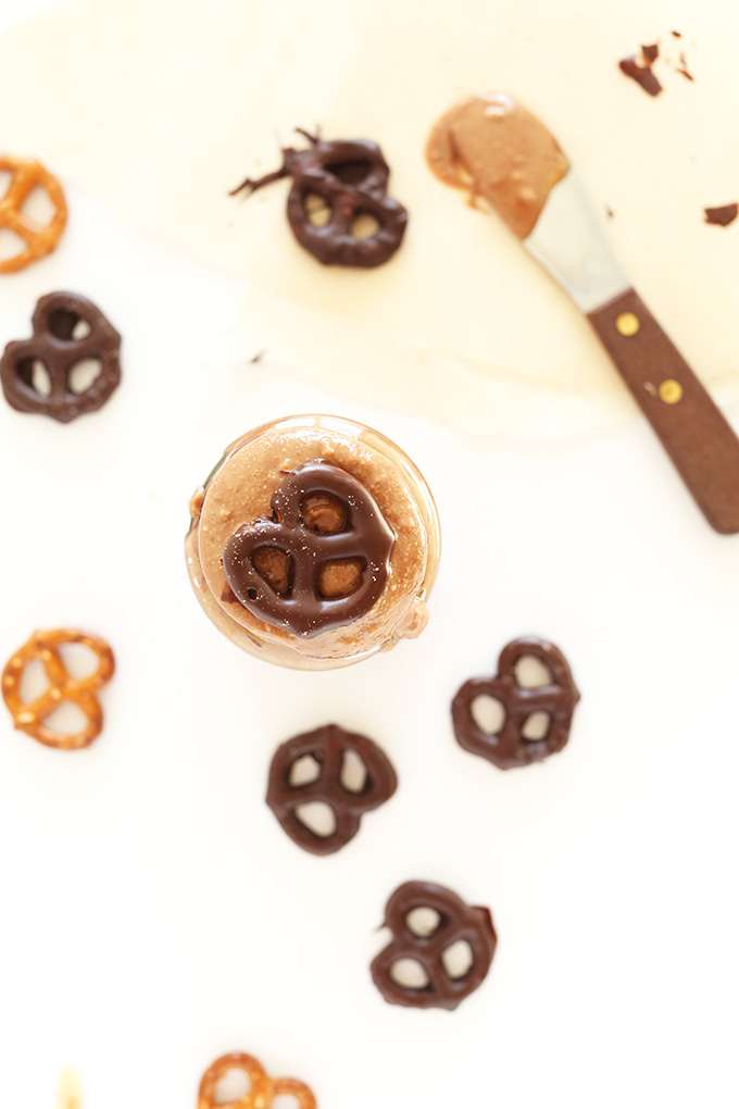 Chocolate covered pretzels surrounding and resting on a jar of Chocolate Pretzel Peanut Butter