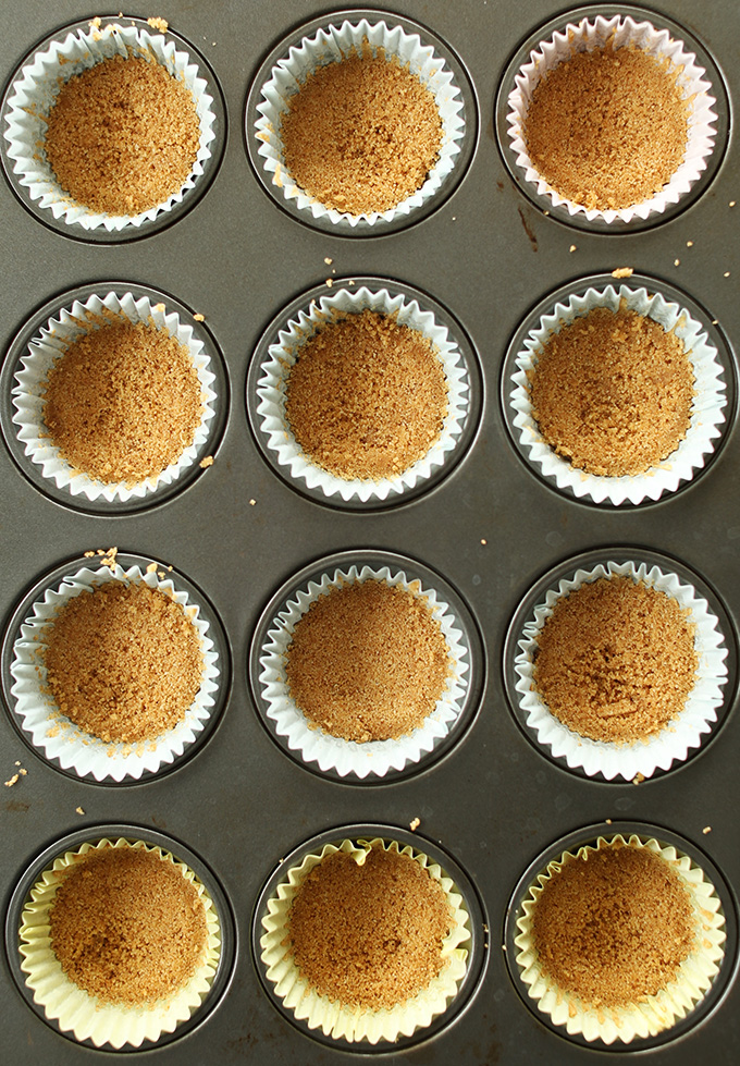 Parchment-lined muffin tins filled with Vegan Graham Cracker Crust