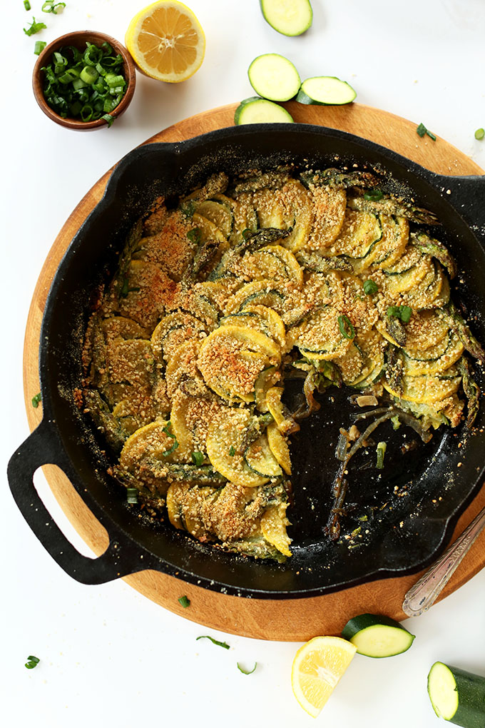 Skillet filled with delicious Vegan Parmesan Gratin alongside ingredients used to make it