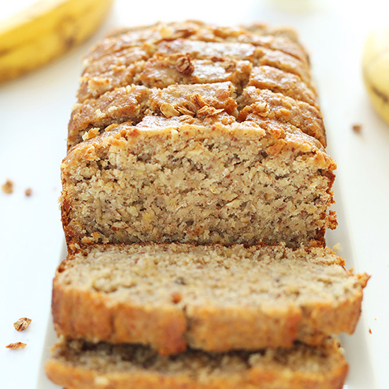 Plate with a partially sliced loaf of Gluten-Free Banana Bread