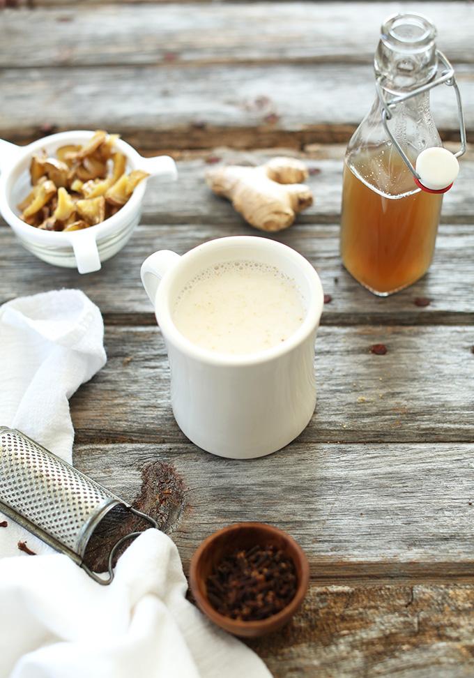 Jarabe de jengibre fresco, trozos de jengibre colado y una taza de nuestra receta de Latte de té de jengibre