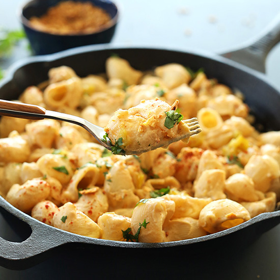 Using a fork to lift a bite of Vegan Green Chili Mac n Cheese from a skillet