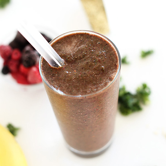 Tall glass of our Hide Your Kale Pomegranate Smoothie recipe beside fresh berries and kale